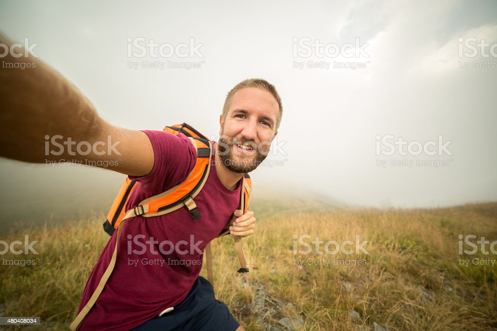 Healthy young man hiking taking selfie stock photo