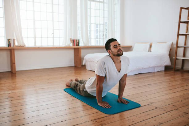Healthy young man practicing yoga at home Indoor shot of handsome young man practicing yoga. Fitness man meditating with his eyes closed while doing cobra pose in living room. cobra pose stock pictures, royalty-free photos & images