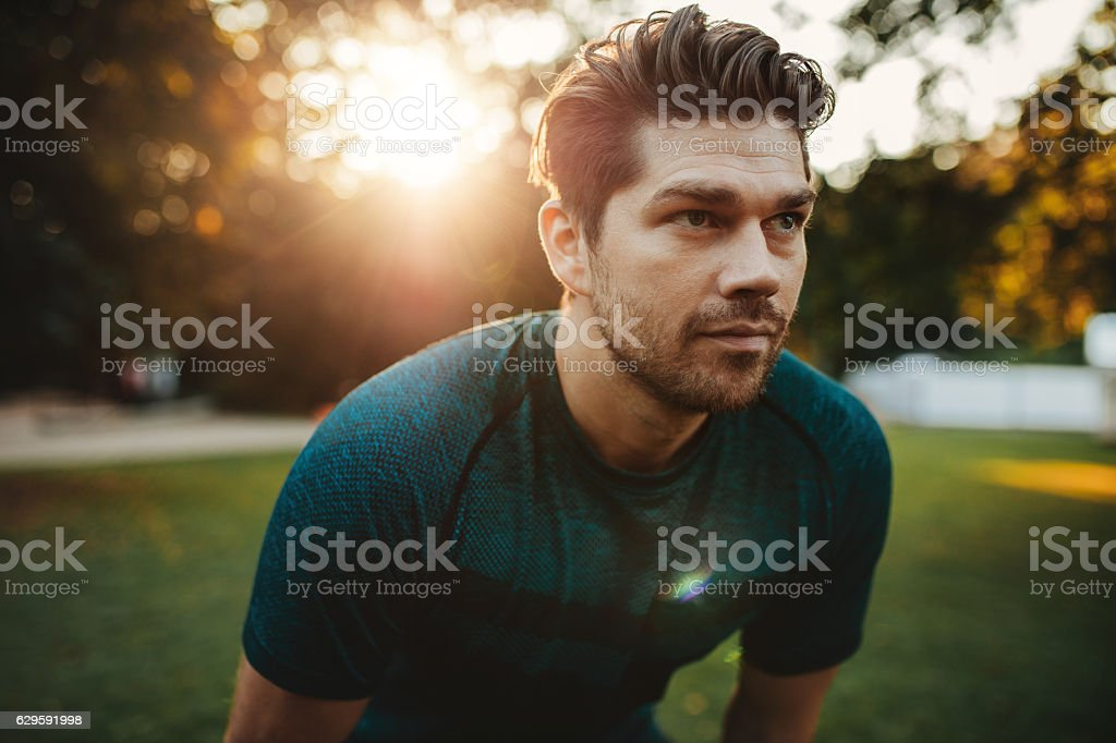 Healthy young man standing outdoors in park stock photo