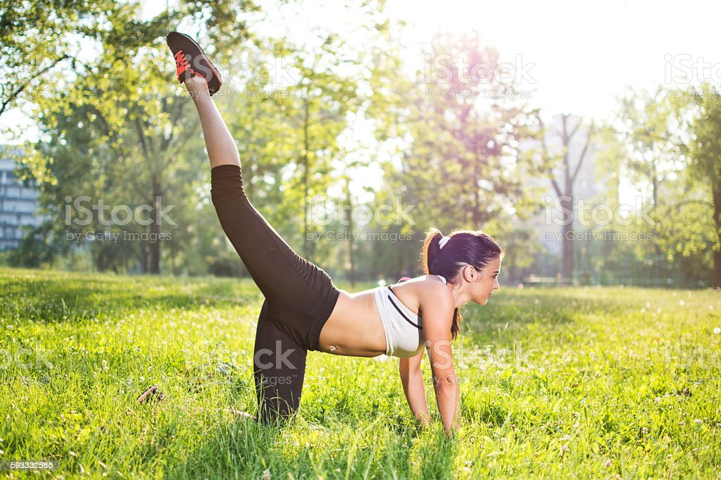 Healthy young sportswoman doing the exercises outdoors. stock photo