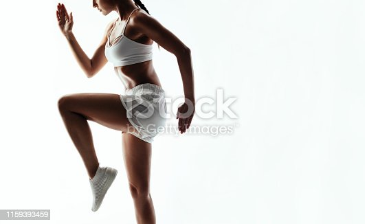 Healthy young woman doing cardio interval training. Fitness female exercising over white background. Cropped shot.