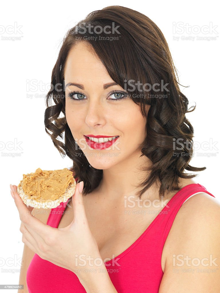 Healthy Young Woman Eating Peanut Butter on a Cracker stock photo