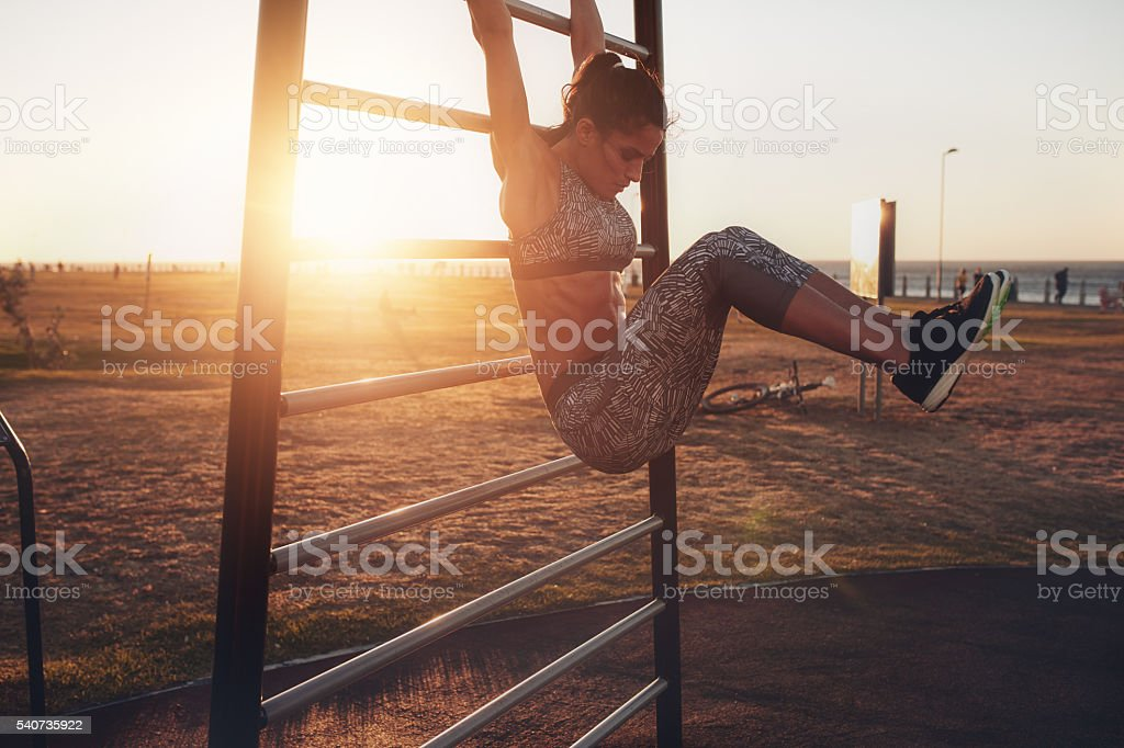 Healthy young woman exercising on wall bars during sunset. stock photo