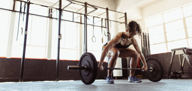 Healthy young woman lifting a barbell stock photo