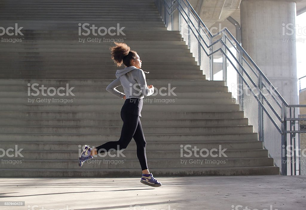Healthy young woman running in urban environment stock photo