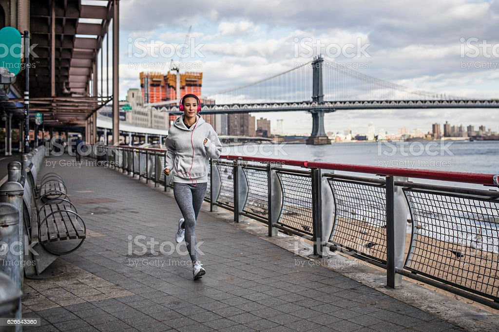Healthy young woman running on promenade stock photo