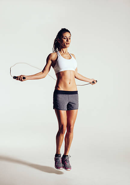 Healthy young woman skipping rope in studio stock photo
