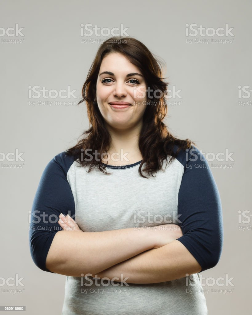 Healthy young woman standing with her arms crossed stock photo