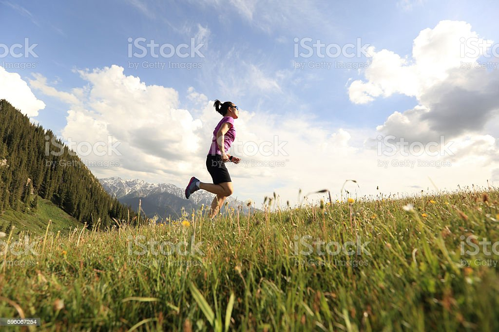 healthy young woman trail runner running on beautiful mountain peak royalty-free stock photo