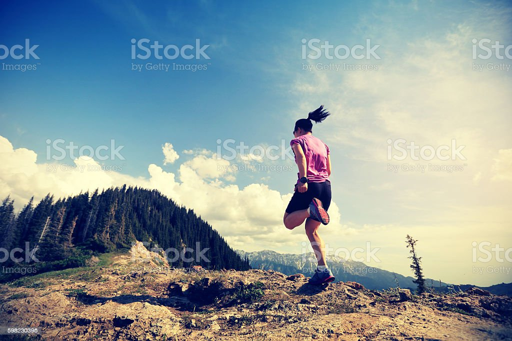 healthy young woman trail runner running on beautiful mountain peak foto royalty-free