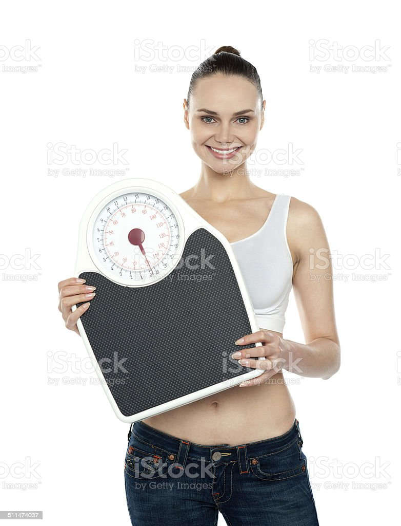 Healthy young woman with a weighing scale stock photo