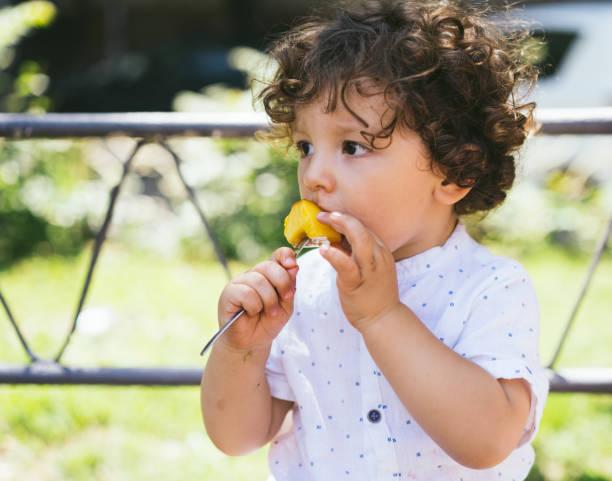 healty children's snack - pesche bambino foto e immagini stock