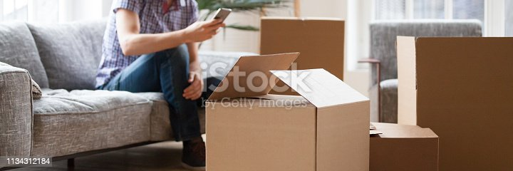 istock Heap cardboard boxes on foreground man with phone on background 1134312184