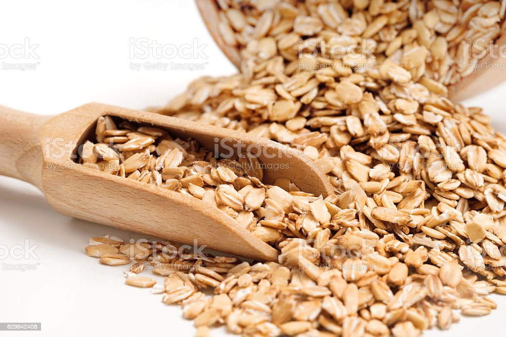 Heap oat flakes and scoop on white background stock photo