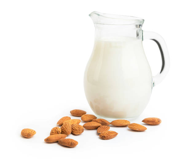 Heap of almond nuts and milk in a glass jar isolated on white background
