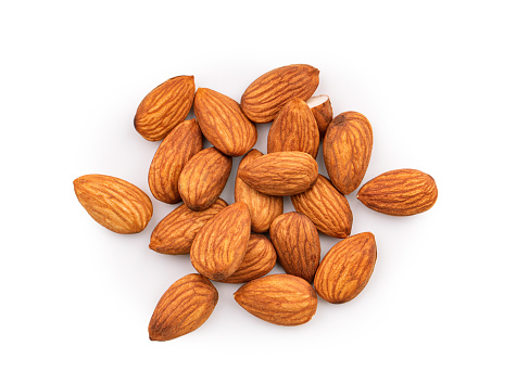 Heap of almonds isolated on white background, top view