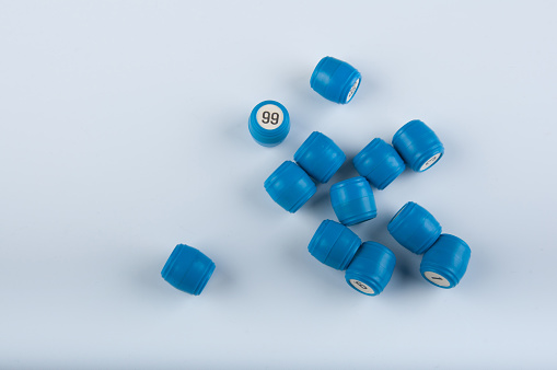 Heap of blue plastic kegs for bingo game with numbers lay on white background
