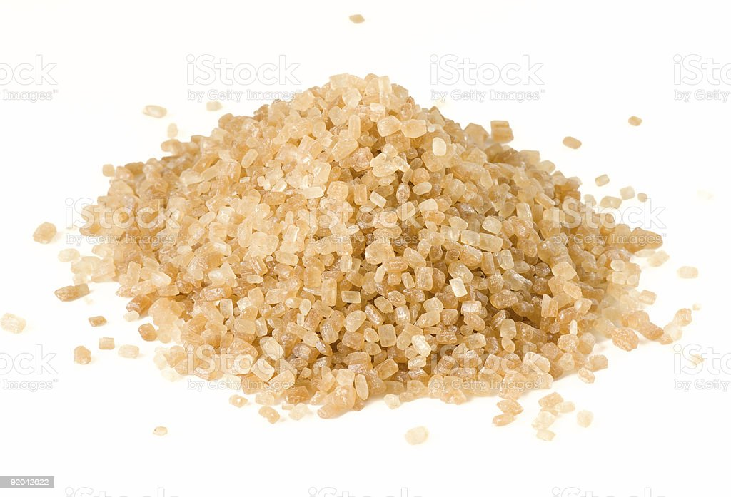 Heap of brown cane sugar isolated on white royalty-free stock photo
