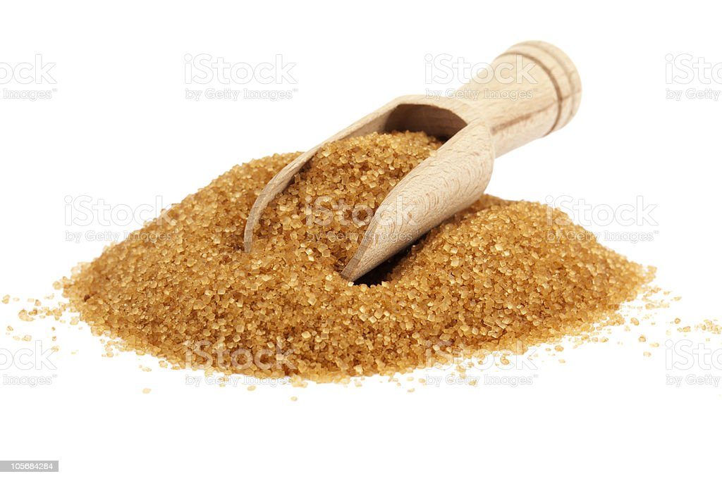 Heap of brown sugar with wooden shovel resting on the top stock photo