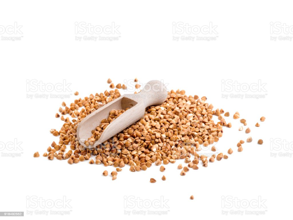 A heap of buckwheat groats, isolated on a white background. Vegeterian and healthy food concept. stock photo