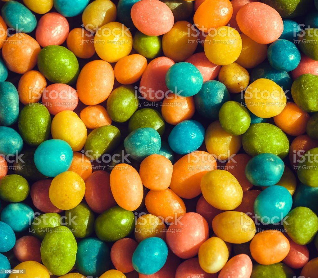 Heap of candy confections small many green, yellow, blue colors. Bright texture and round forms of sweets in sugar stock photo