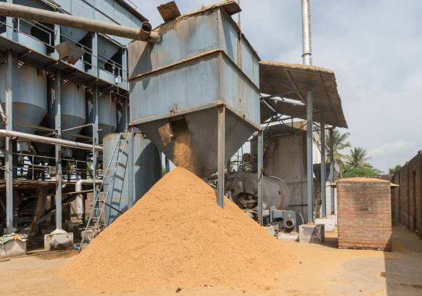 Heap of chaff falling out container at rice mill, India. stock photo