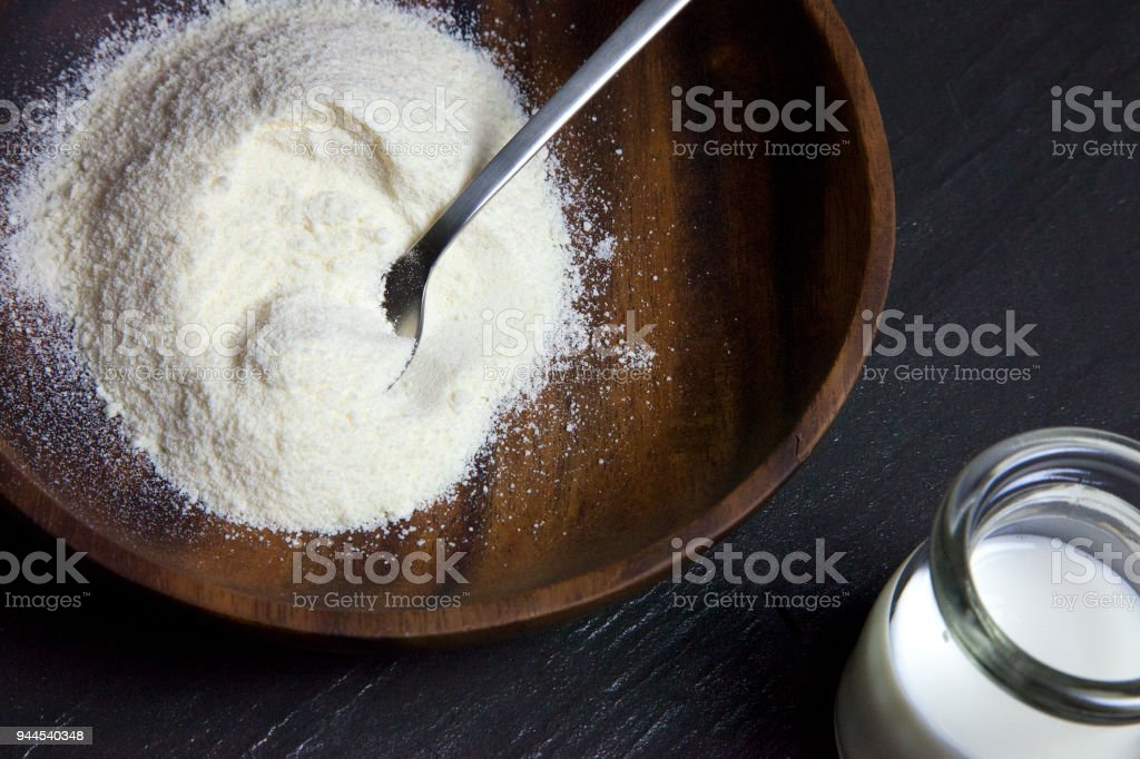 Heap of cheese powder on wooden plate with a bottle of milk black...