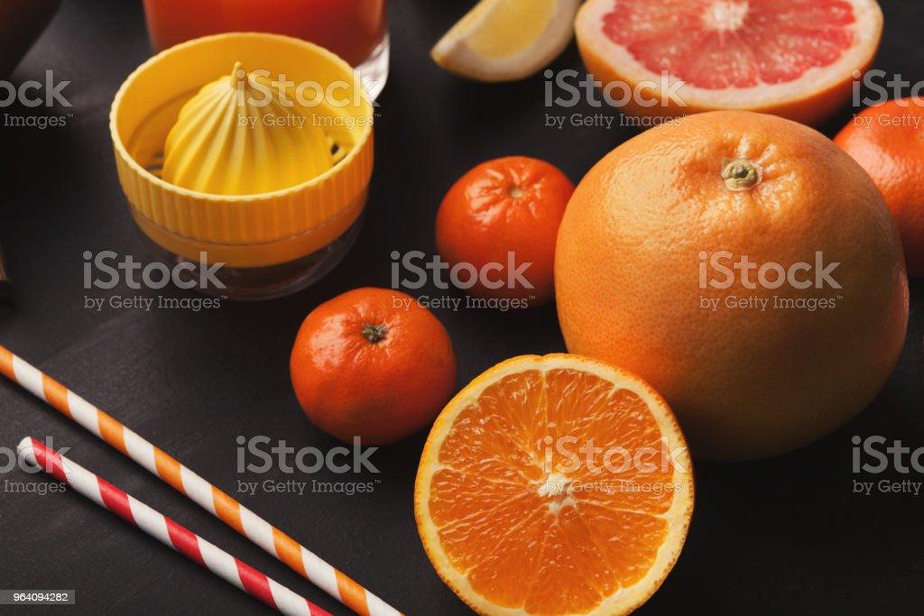 柑橘類と黒い背景にジュース ガラスのヒープ - かんきつ類のロイヤリティフリーストックフォト