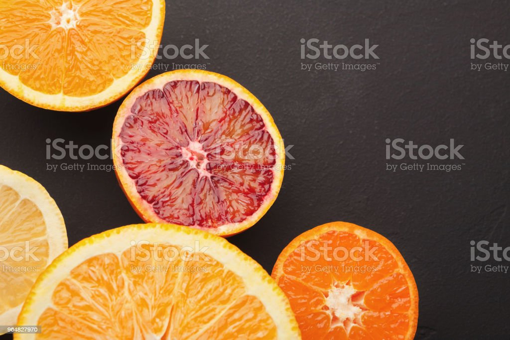 Heap of citruses and juice glass on black background royalty-free stock photo