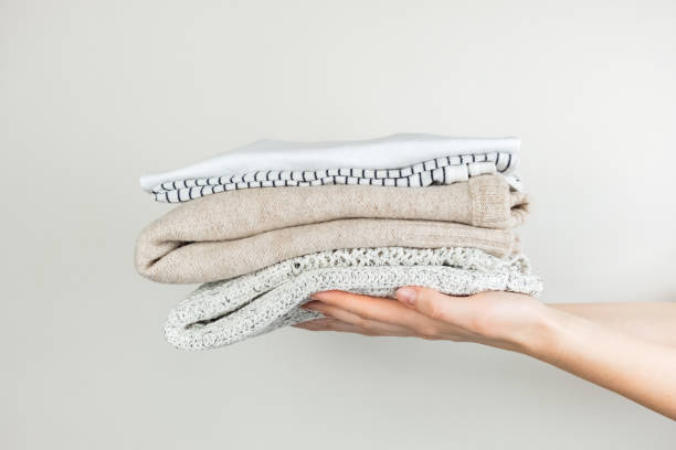 Heap of clothes in female hands Neatly stacked simple clothing at white background clothing stock pictures, royalty-free photos & images