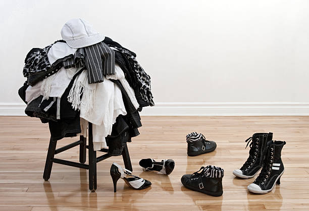 Heap of clothing on a stool and disordered shoes stock photo