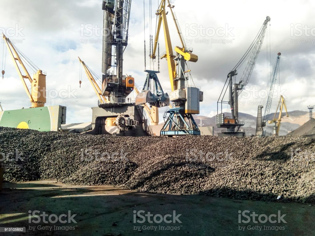 Heap of coal anthracite in the port. Port cranes for coal loading stock photo