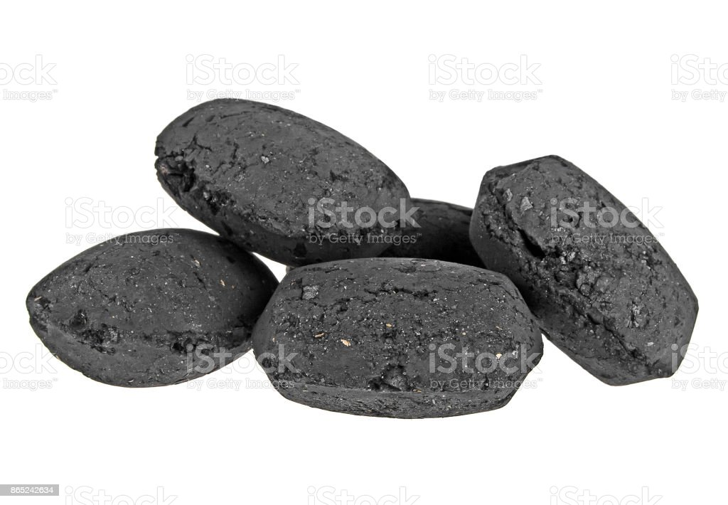 Heap of coal briquette for BBQ isolated on white background stock photo