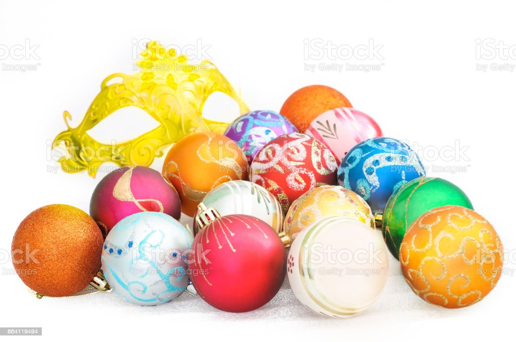heap of colorful christmas baubles and carnival mask on white background royalty-free stock photo