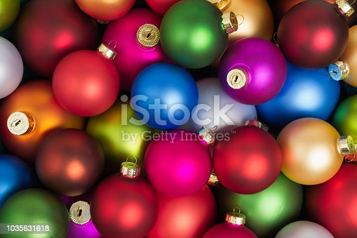 A heap of colorful christmas baubles lying on the floor in flat lay.