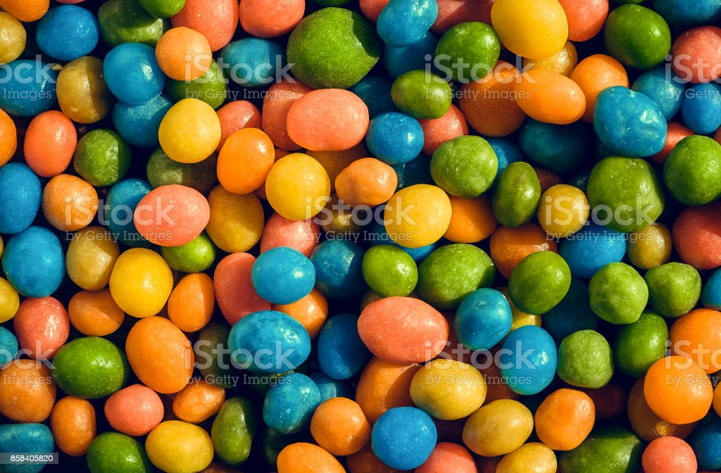 Heap of crazy colors candies with small green, yellow, blue pieces. Bright texture and round forms of sweets in sugar stock photo