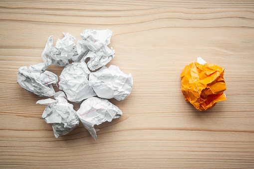 istock Heap of crumpled white paper balls with one different orange paper ball against them. Concept of think different, think out of the box, leadership.  Illustration of baiting. 1146260775