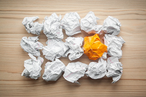 istock Heap of crumpled white paper balls with one different orange paper ball between them. Concept of think different, think out of the box, leadership. 1146260789