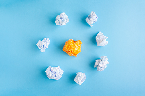 istock Heap of crumpled white paper balls with one different orange paper ball between them. Concept of self isolation and social distance caused by coronavirus, think different 1222169786