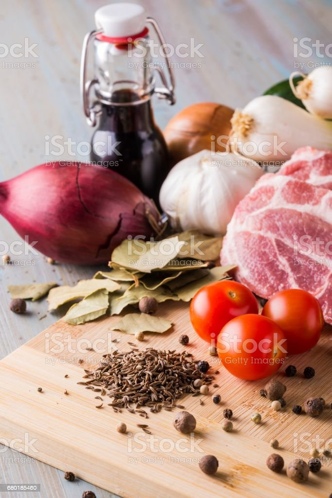 Heap of cumin spice next to pork meat and vegetable stock photo