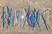 Heap of different plastic waste: straws and single-use spoons, toothbrush and comb collected on the beach on sand background. Environmental pollution problem, a lot of disposable waste, say no plastic