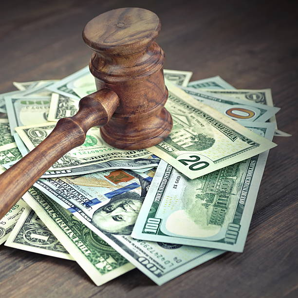 Heap Of Dollars With Judges Or Auctioneers Gavel Or Hammer stock photo