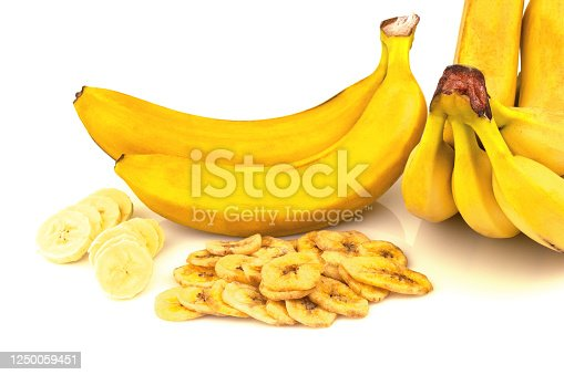 Macro view of heap of dried banana chips with banana bunch on white background