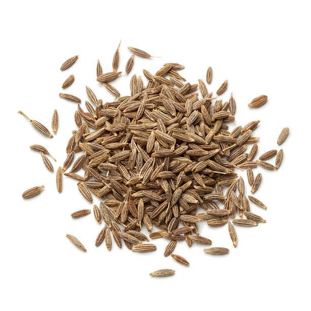 Heap of dried cumin seeds stock photo