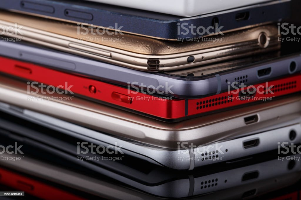 Heap of electronical devices close up - smartphones on black background stock photo