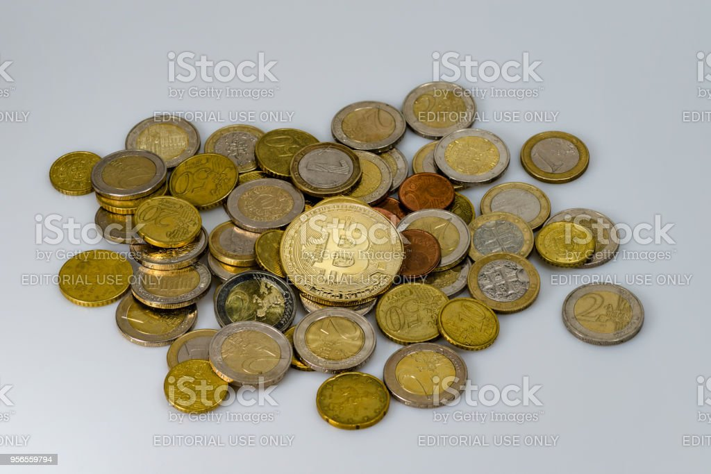 Ein Haufen von Euro-Münzen aus verschiedenen Ländern und ein Bitcoin auf einem weißen Hintergrund – Foto
