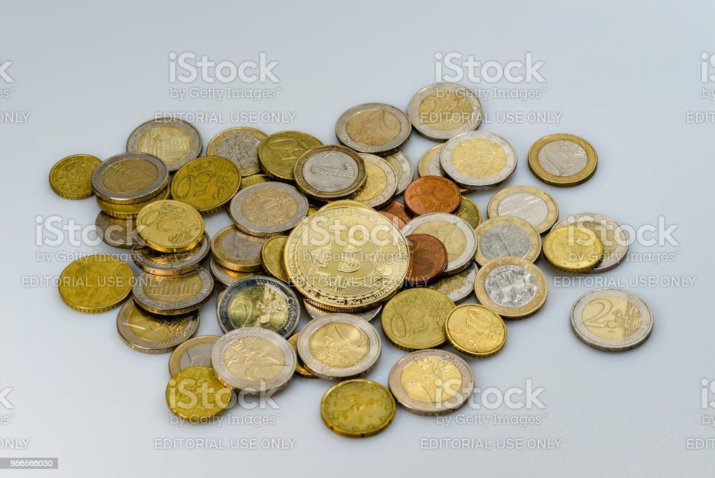 Ein Haufen von Euro-Münzen aus verschiedenen Ländern und ein Bitcoin auf einem weißen Hintergrund (verschiedene Licht-Setup) – Foto