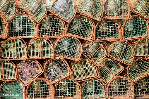 Heap of large group of fishing net baskets on a harbor dock.