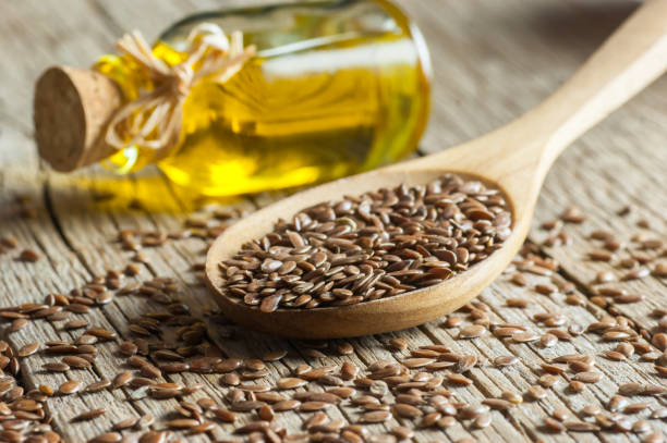 heap of flax seeds or linseeds in spoon and bowl with glass of linseed oil on wooden backdrop. flaxseed or linseed concept. flax seed dietary fiber - dieta macrobiotica foto e immagini stock