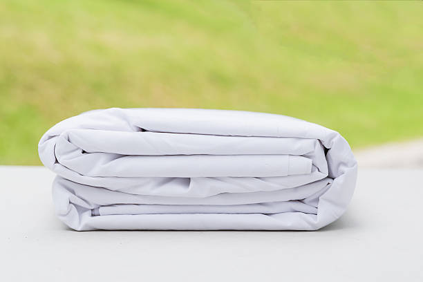 heap of folded white cloth fabrics on wooden table stock photo
